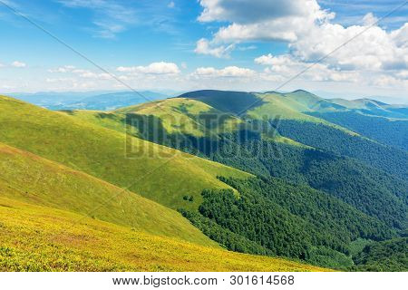 Beautiful Summer Landscape In Mountains. Ridge Rolling In The Distance. Sunny Weather. Fluffy Clouds