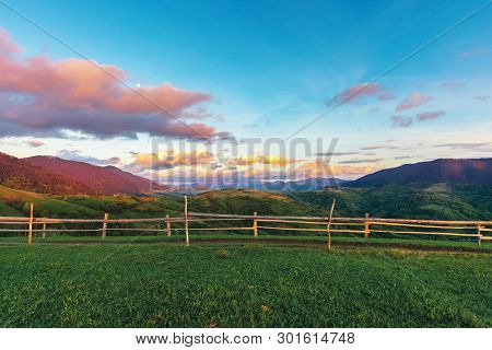 Beautiful Rural Area In Mountains At Sunset. Agricultural Fields On Hills. Ridge In The Distance. Fe
