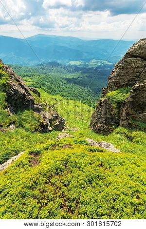 Summer Nature Scenery In Mountains. Huge Boulders On The Edge Of A Grassy Slope. Ridge Behind The Va