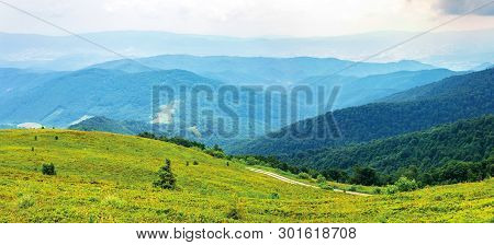 Mountain Panorama On Cloudy Summer Noon.  Road Winds Uphill Green Meadows. Beautiful Nature Landscap