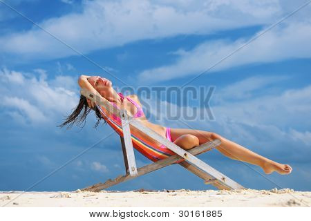 Girl on a tropical beach sitting in chaise lounge