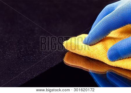 Hand In Protective Glove Wiping Dust Layers On The Furniture  With Yellow Dry Rag. General Or Regula