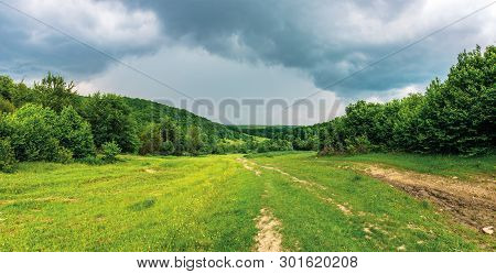 Panorama Of A Summer Countryside In Mountains. Path Through Meadow Between Forest. Cloudy Sky Before