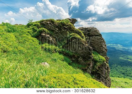 Summer Nature Scenery In Mountains. Huge Rocky Formation On The Edge Of A Grassy Slope. View In To T