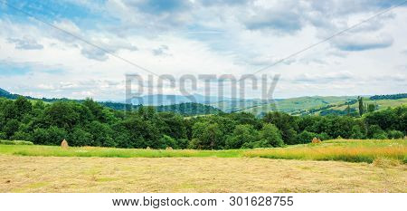 Panorama Of A Countryside In Mountain On A Cloudy Day. Beautiful Landscape With Rural Hay Fields On