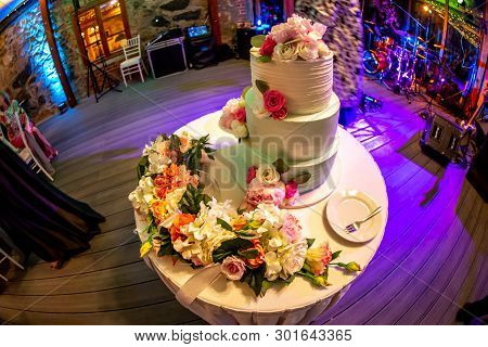 Wedding cake decorated with flowers on table. Three tiered wedding cake and plate with fork on white table. Shot with fisheye lens. poster