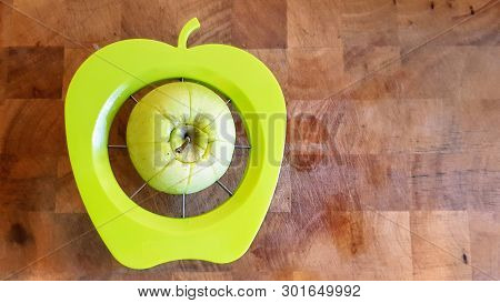 A Green Apple Being Separated Into Chunks By A Green Apple Shaped Slicer, Divider And Corer On A Woo