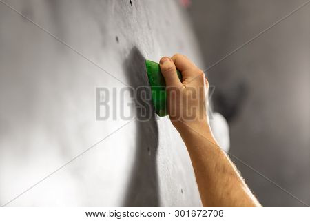 fitness, extreme sport, bouldering, people and healthy lifestyle concept - close up of male hand holding to indoor climbing wall