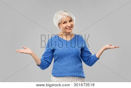 old people concept - smiling senior woman in blue sweater shrugging or presenting something imaginary over grey background
