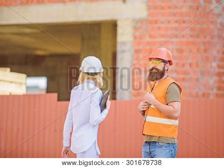 Construction Site Safety Inspection. Discuss Progress Project. Woman Inspector And Bearded Brutal Bu