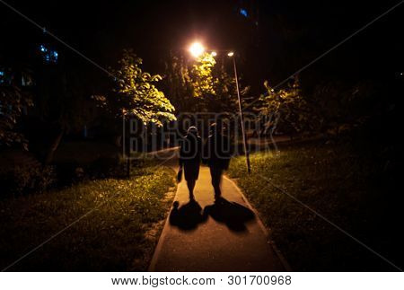 Soft Focus Blurred Image Of A Man And A Woman Are Walking Along The Road At Night. Spouses Go Holdin