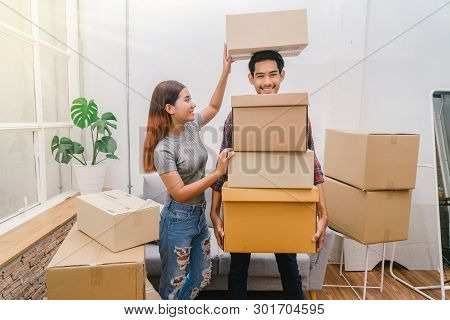 Asian Young Couple Carrying Big Cardboard Box For Moving In New House, Helping Relocate And Joshing