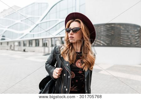 Gorgeous Red-haired Hipster Young Woman In Dark Sunglasses In An Elegant Hat In A Stylish Black Leat