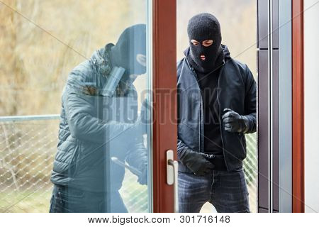 Two burglars open patio door from home while breaking in with a crowbar