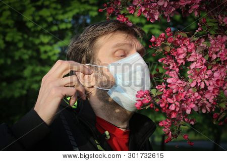 A Man In A Medical Mask Sneezes From Pollen. Seasonal Allergic Reaction To Pollen