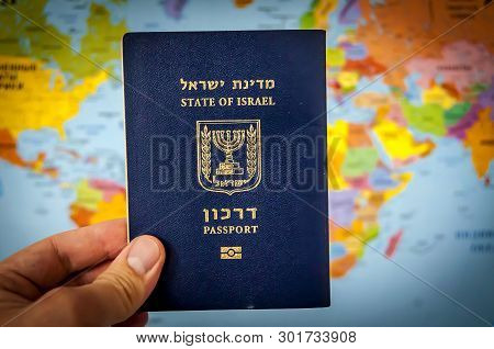 Hand Holding The Passport Of The State Of Israel Against The Colorful World Map Atlas. Israel Citize