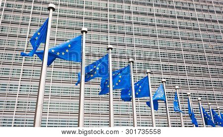 The Queue Of Steeples With Blue Flags Of The European Union Against The Background Of The European C