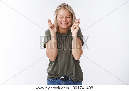 Wish me luck. Excited optimistic attractive woman hope today boyfriend make proposal crossing fingers for good luck smiling with closed eyes and thrilled emotions over white background poster