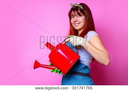 Image of happy florist woman with watering can in hand