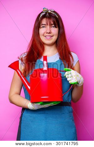 Photo of happy florist brunette woman with watering can in hand