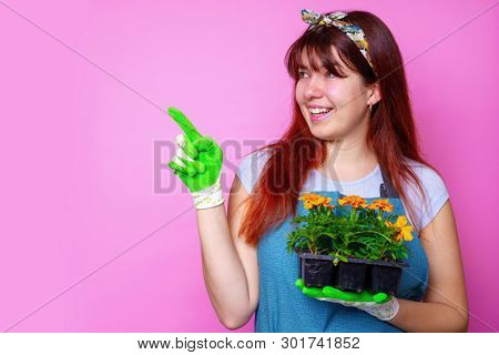 Photo of happy woman with marigolds , pointing to side