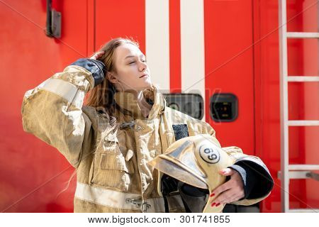 Photo on side of fire blonde woman standing near fire truck