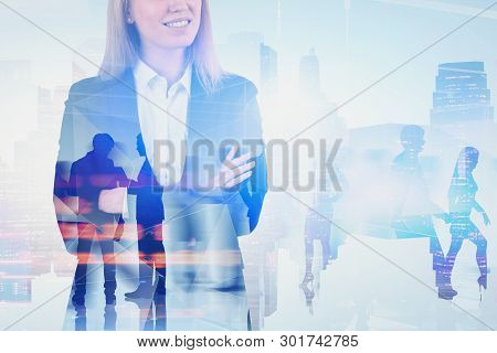 Blonde Businesswoman With Crossed Arms Standing Over Cityscape Background With Double Exposure Of Bu