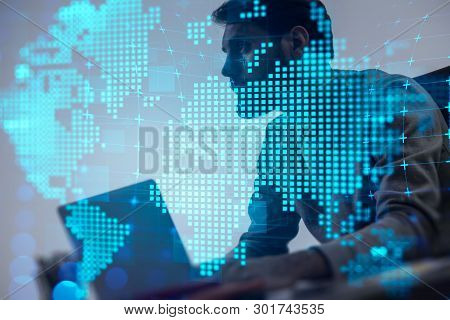 Pensive Young Man In Casual Clothes Using Laptop With Double Exposure Of Digital World Map. Concept