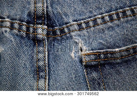 Back Side Of Double Sewn Seams And Frayed Hole On Pocket Of Old Blue Jeans
