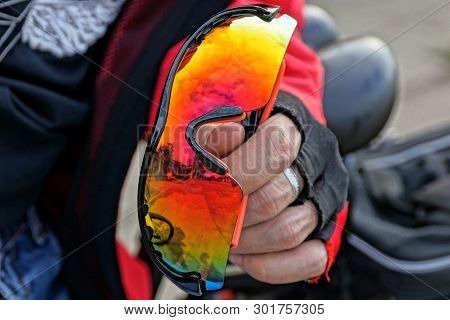 Gloved Hand Holds Colored Sport Glasses Outside