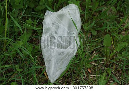 Trash From White Empty Plastic Bag Lies On The Green Grass In Nature