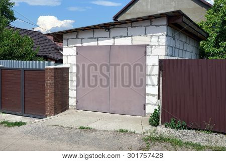 White Brick Garage With Brown Gates And Metal Fence On The Street By The Road