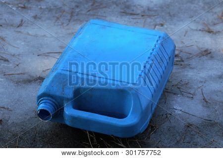 Trash From One Plastic Dirty Blue Canister Lies On The Ice In The Street