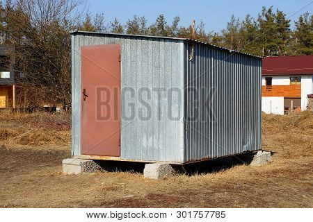 Gray Metal Trailer With A Brown Door Standing Outside In The Dry Grass