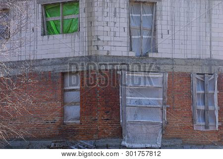 Wall Of An Unfinished House Of Gray And Brown Bricks With Windows