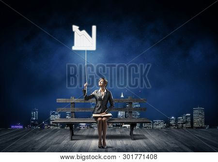 Young Woman With Open Book On Wooden Bench Outdoor. Beautiful Girl In Business Suit Holding Growing