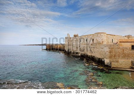 The Coastal Line Of The Central Part Of The Sicilian Town Of Syracuse On The Background Of The Blue