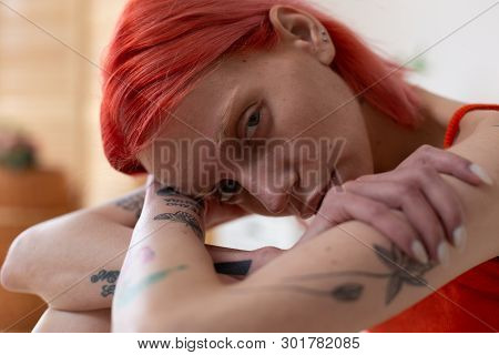 Red-haired Woman With Tattoos Feeling Pain And Misery