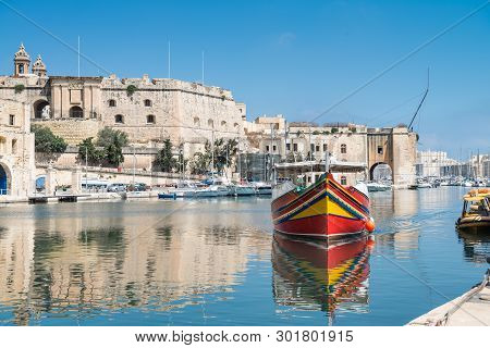 Traditionally Painted Passenger Boat Transports Passengers Between Valetta And Vittoriosa In Grand V