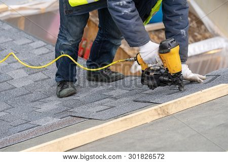 Close Up And Real Photo Of Professional Roofer Worker In Uniform Work Wear Using Air Or Pneumatic Na