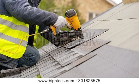Unrecognizable Roofer Worker In Special Protective Work Wear And Gloves, Using Air Or Pneumatic Nail