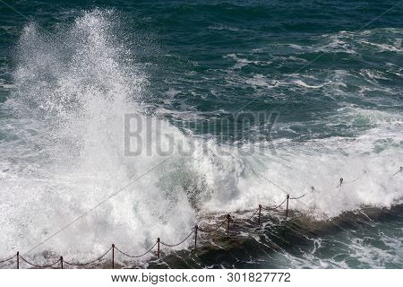 Waves Crashing Over The Bogey Hole, A Swimming Hole Carved Into Rocks By Convicts In Newcastle, Aust