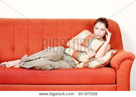 Woman With Headache Laying On Sofa At Home