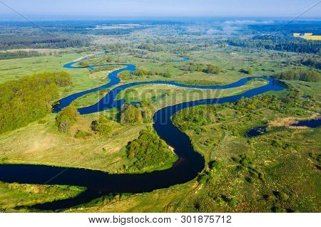 Aerial Nature River Background. Scenic River On Green Meadow From Above. Drone View On Curved River