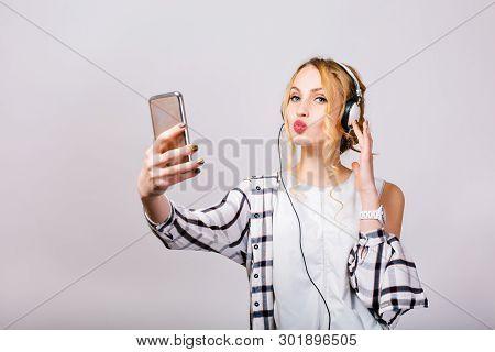 Gorgeous Cute Young Woman Taking Selfie Near Grey Wall, Looking At Smartphone, Sending Kiss. Mirthfu
