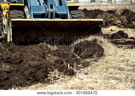 Bulldozer Pushes The Ground, Tractor Pushes A Lump Of Soil, Preparing The Area For Construction.
