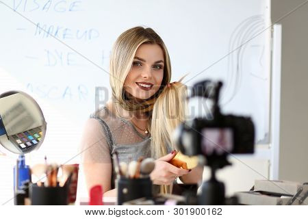 Young Blogger Recording Video Beauty Workshop. Caucasian Blond Girl Broadcast Haircare Vlog. Maquillage Master Styling Hair with Hairbrush by Camera. Attractive Vlogger Job Concept poster
