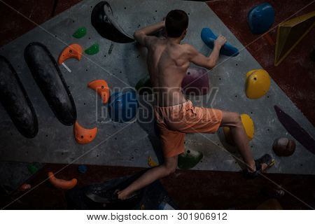Athletic man practicing in a bouldering gym