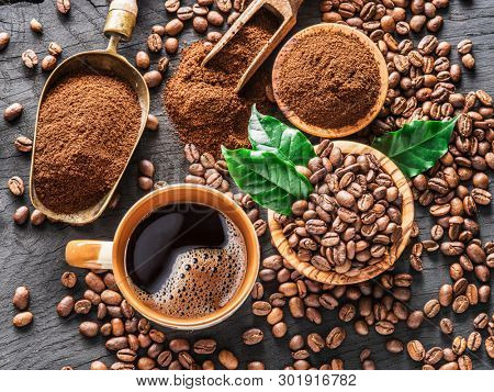 Roasted coffee beans, ground coffee and cup of coffee on wooden table. Top view.