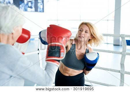 Blonde aggressive woman in activewear and boxing gloves hitting her older rival during training on the ring